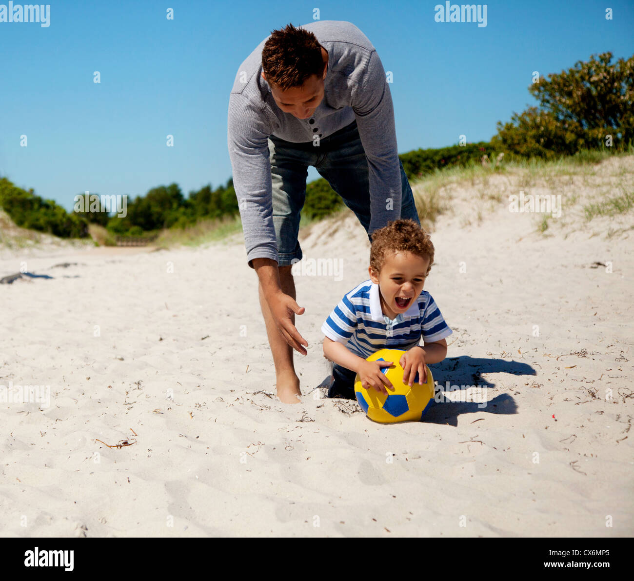 Excited kid grabs the ball as he plays a soccer game with his father - Stock Image