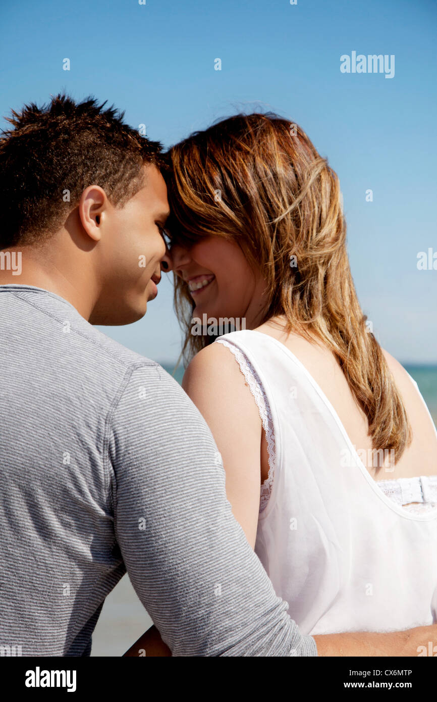 Couple looking at each other's eyes against blue background - Stock Image