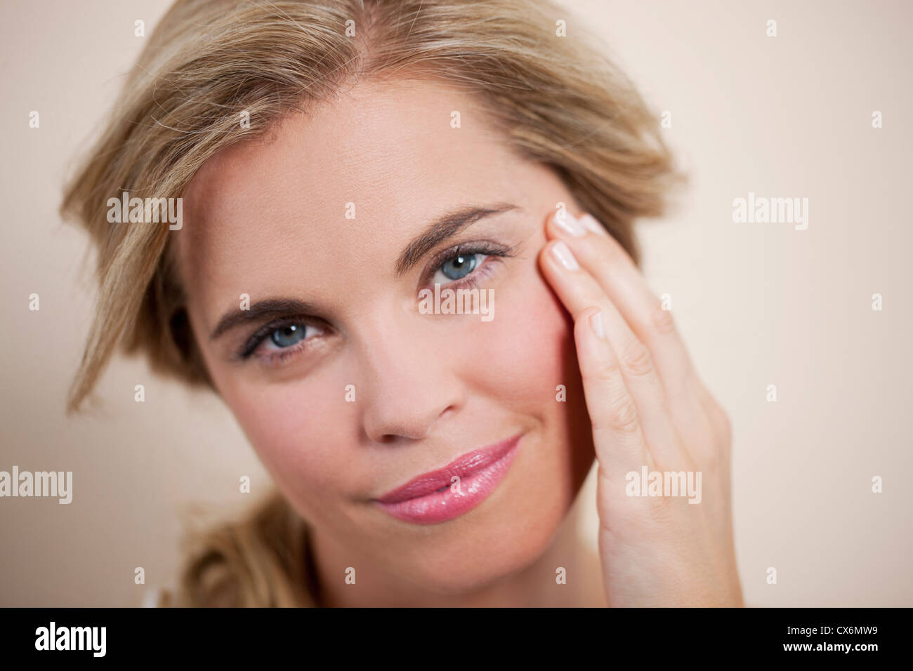 A young blonde woman touching her face, smiling - Stock Image