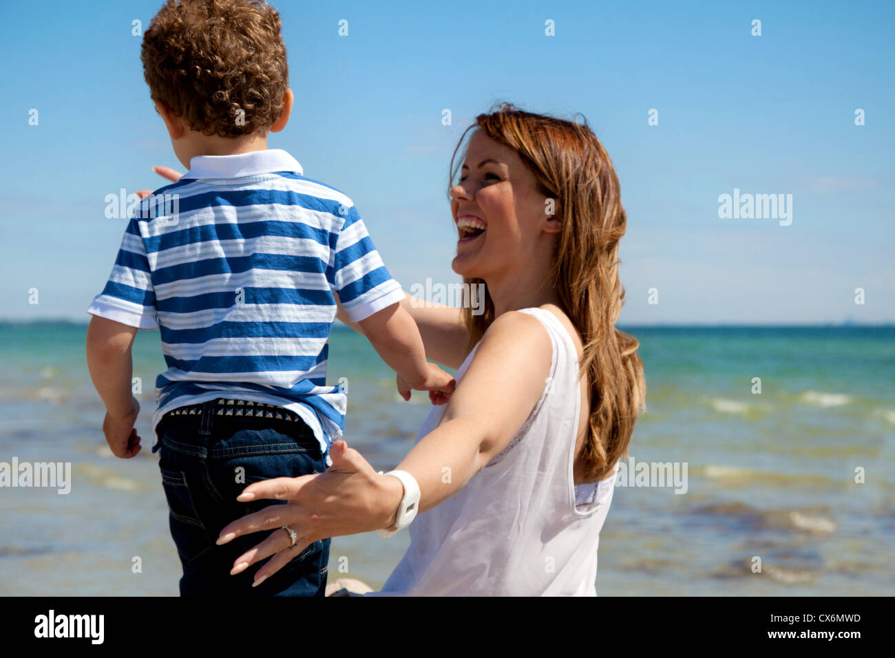 Young mom enjoys the beach as she looks at her son with delight - Stock Image