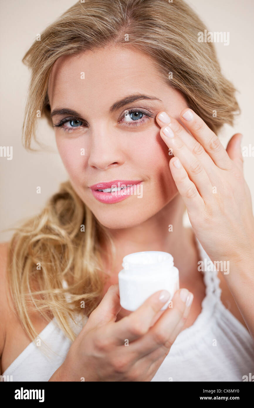 A young blond woman applying moisturizer to her face, close up - Stock Image