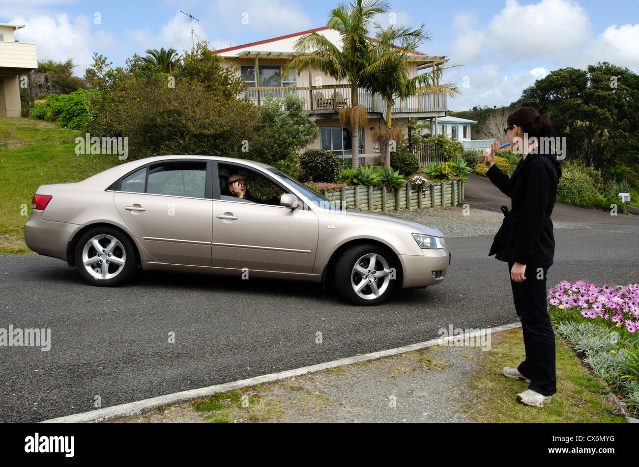 A very old man with a valid driving license drives his car while saying goodbye to his grandchild. Stock Photo