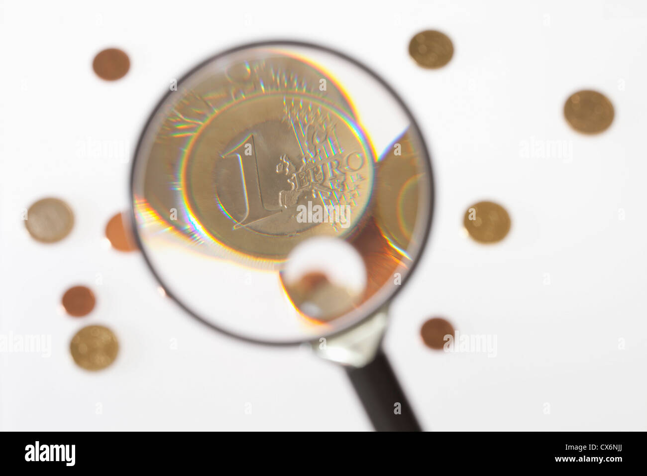 A magnifying glass magnifying a one Euro coin - Stock Image