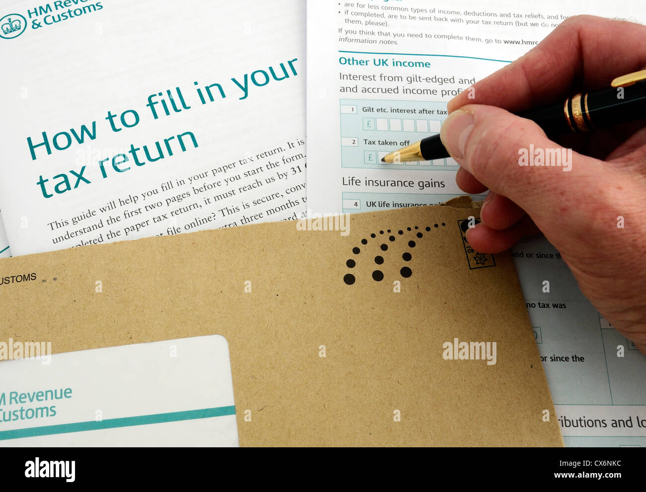 A man filling in an income tax return form, uk - Stock Image