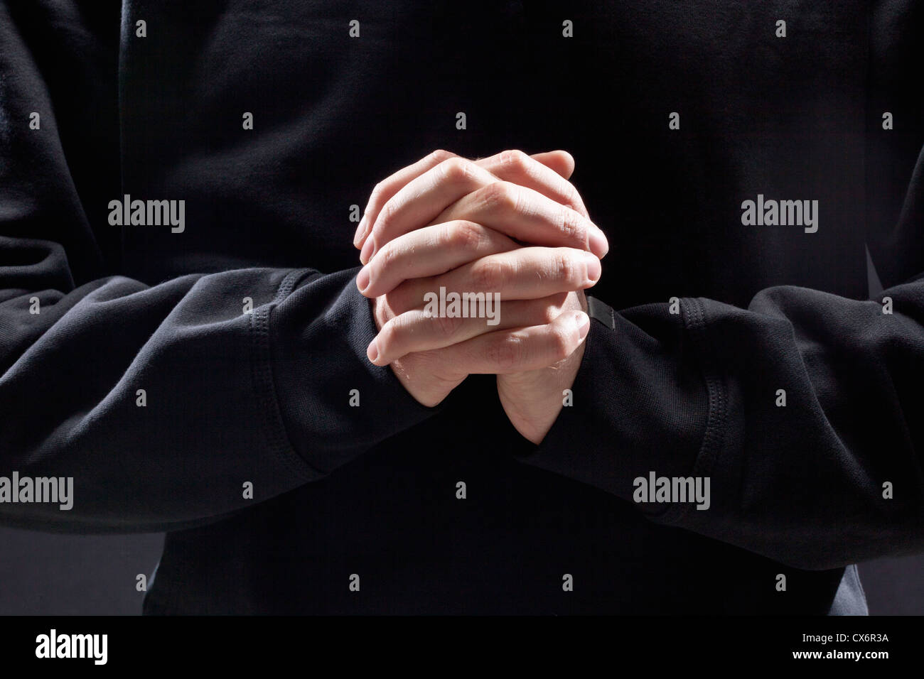Man with clasped hands - Stock Image