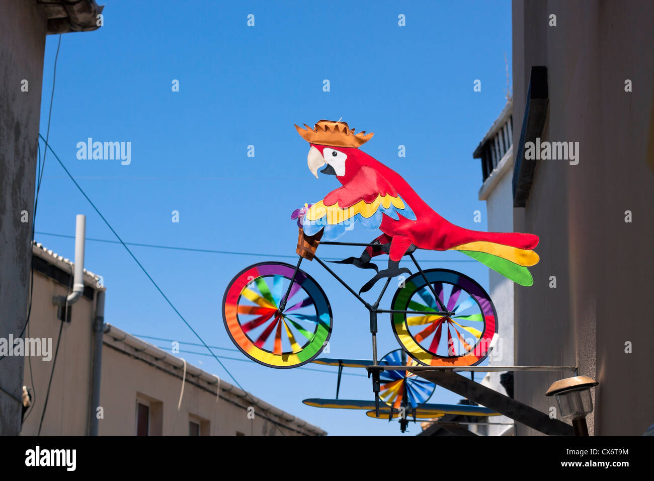 Colourful whirligig, parrot on the bicycle, house exterior decoration. - Stock Image