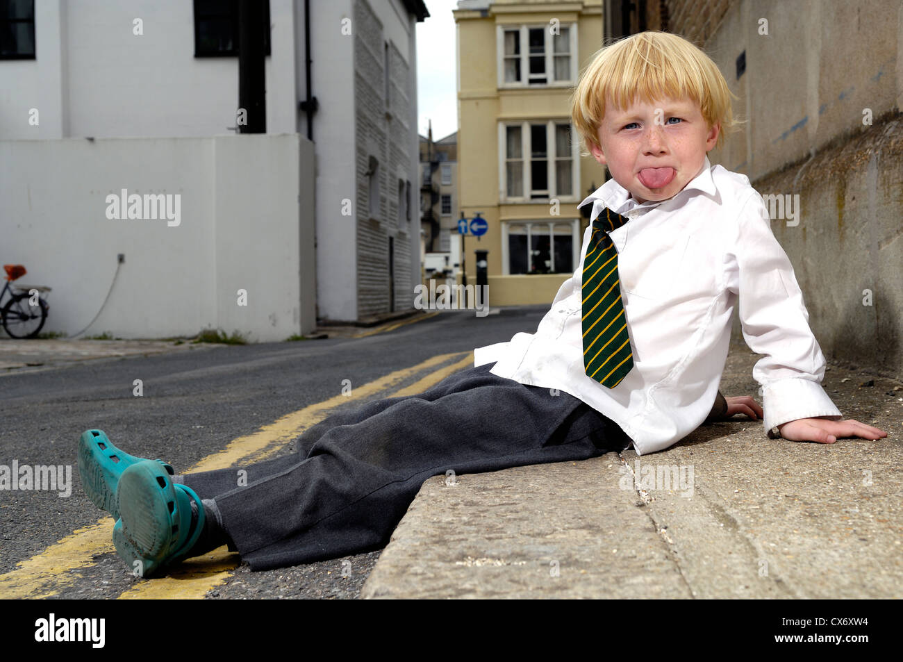 Boy Sitting on Curb - Stock Image