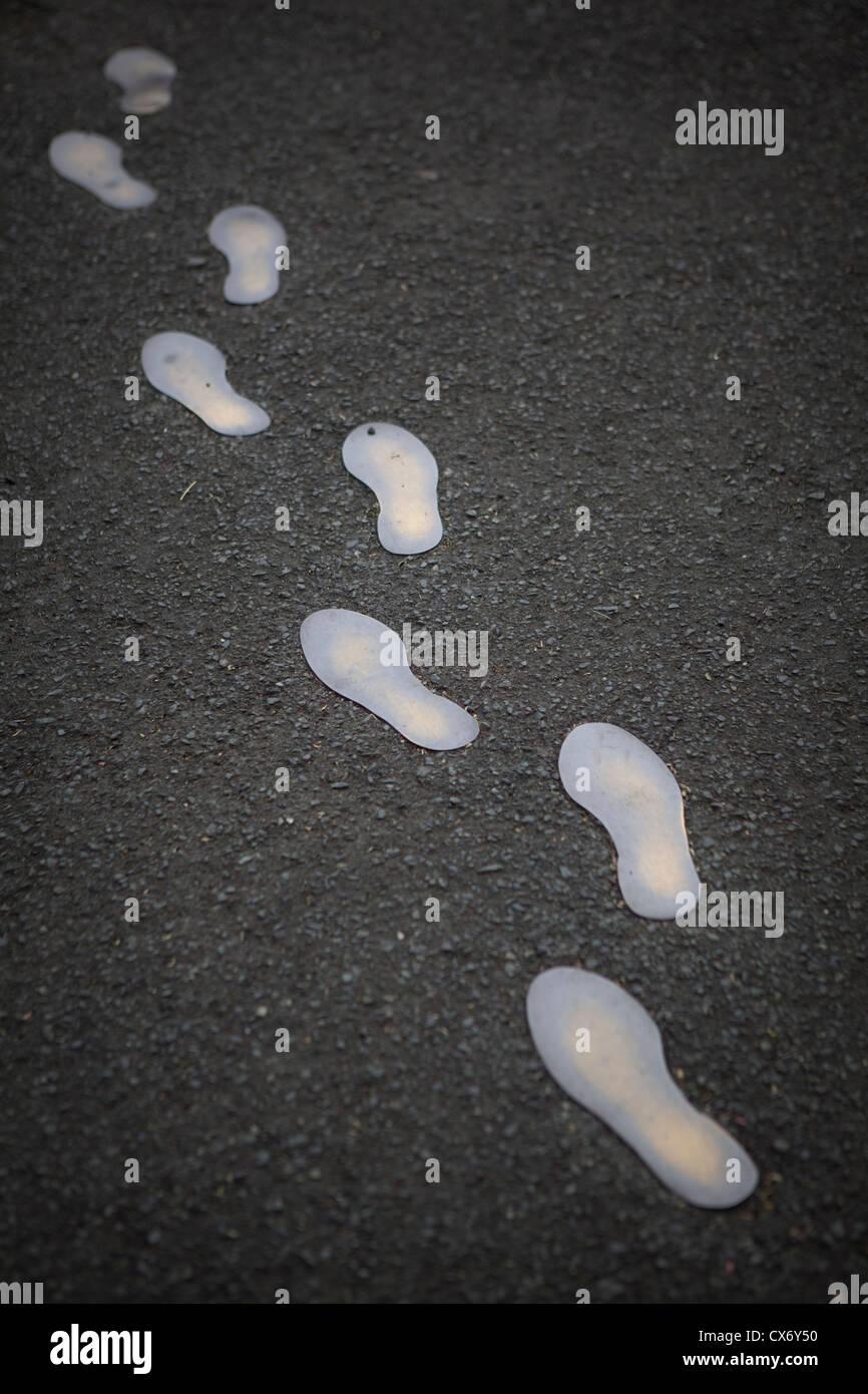 A white footprint path on a black street. - Stock Image