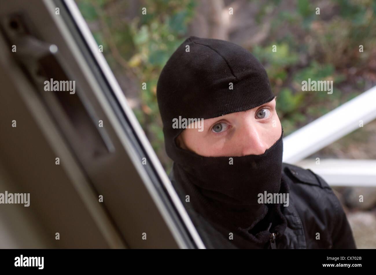 Burglar looking through house window - Stock Image