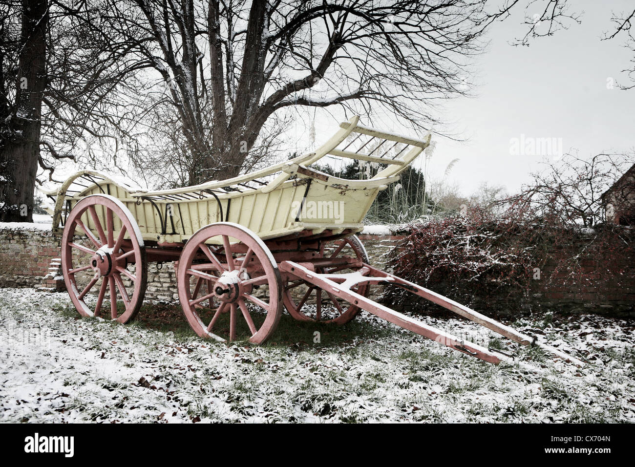 English Farm Cart, horse drawn waggon in the snow in Oxfordshire, England. The grass and old brick wall is frosty - Stock Image