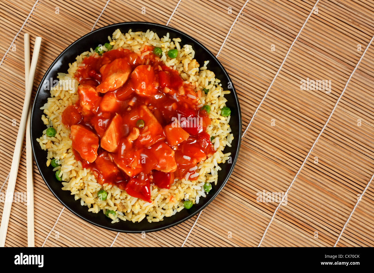sweet and sour chicken with fried rice - popular oriental cuisine - Stock Image