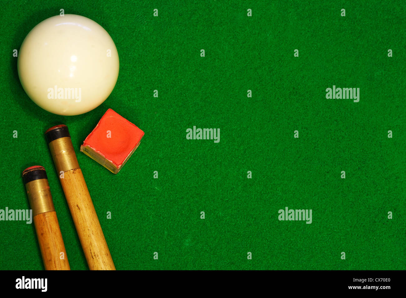 A green cloth billiards or pool table background with cues, cueball and chalk - Stock Image