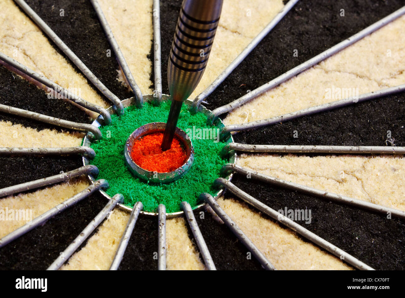 a dart hits target in the centre of a darts board good business concept for success - Stock Image