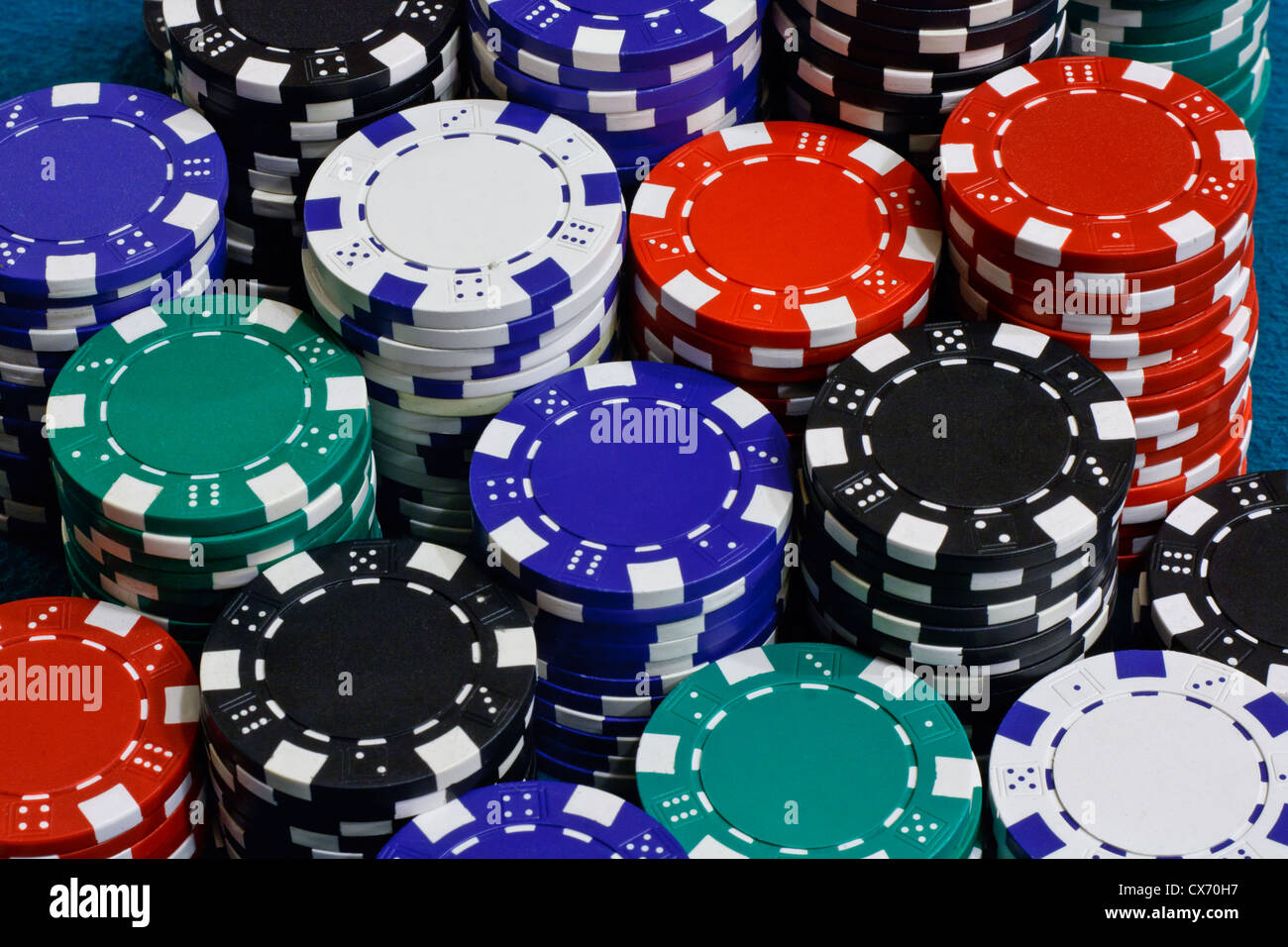 Poker chips stacked on card table - Stock Image