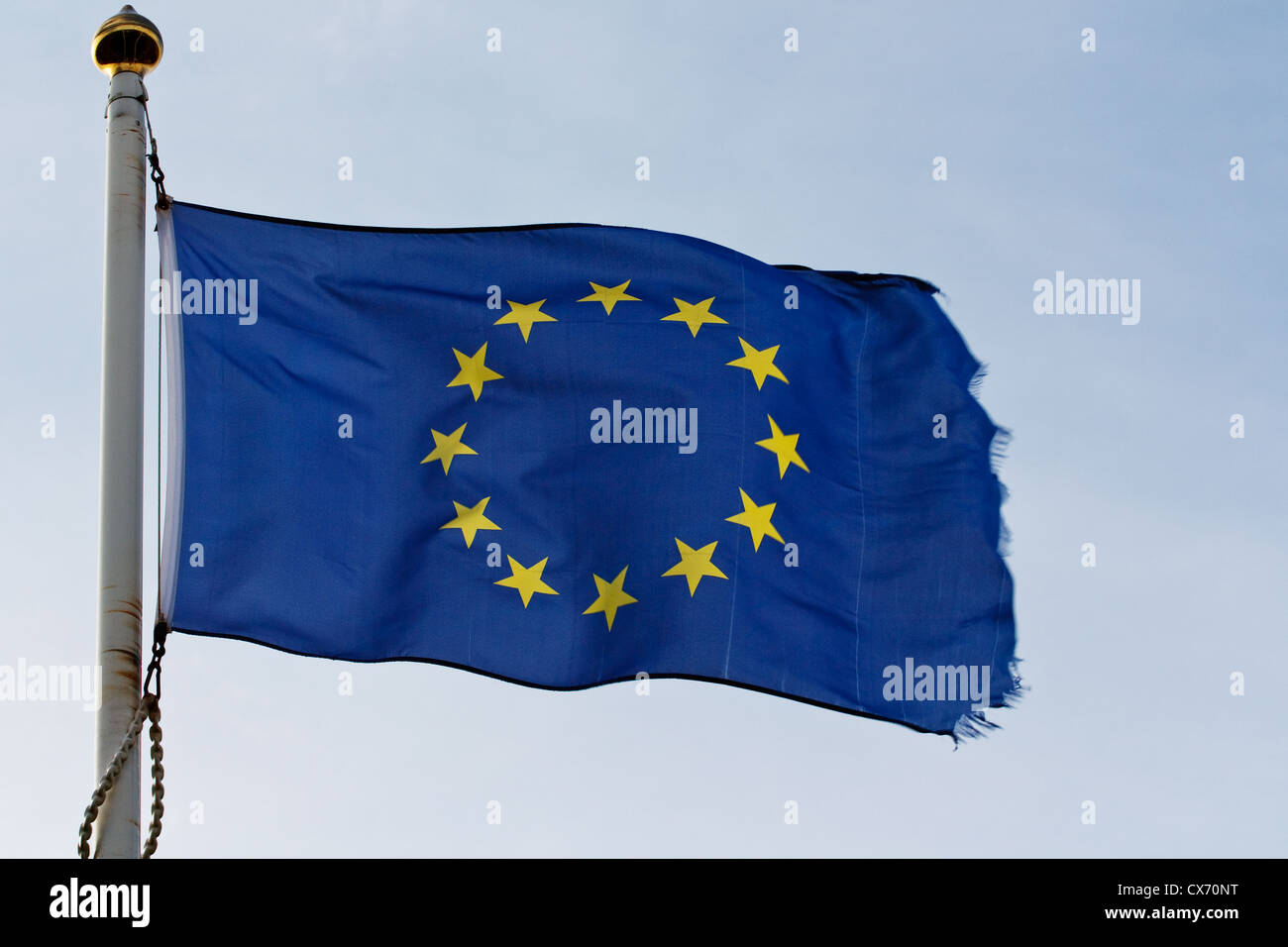 The European union flag of europe ripples in the wind on flagpole - Stock Image
