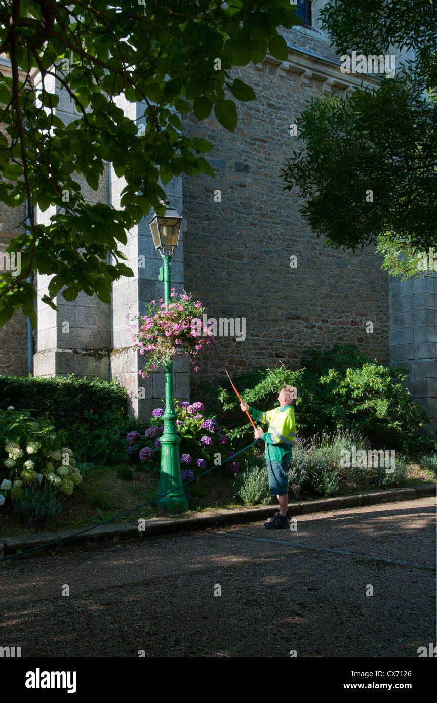 Man watering hanging basket at Saint-Pierre-des-Nids village, Mayenne, Pays de la Loire, France. Europe. - Stock Image