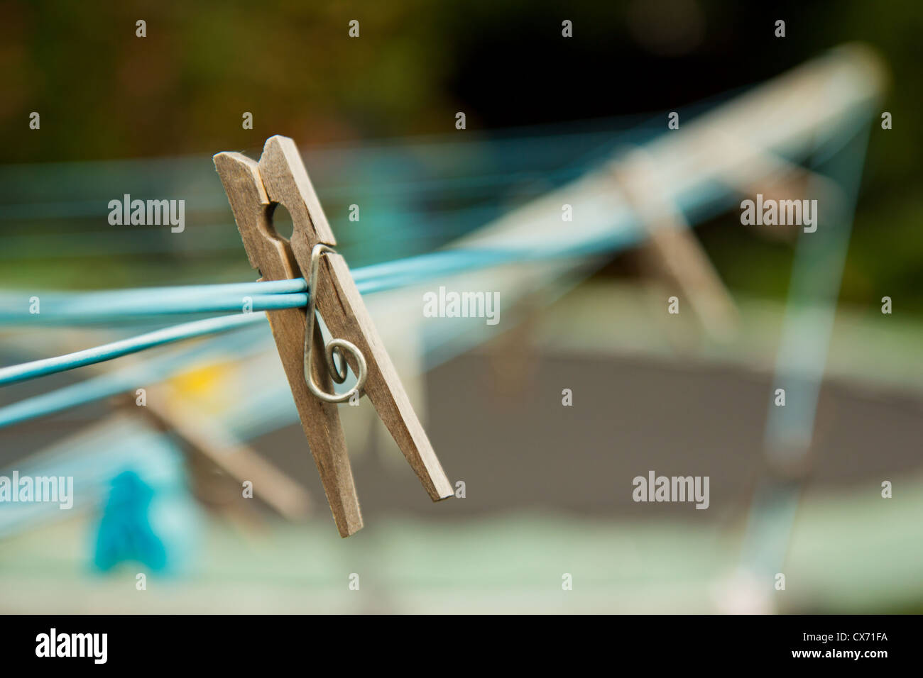Wooden clothes peg on a blue washing line - Stock Image