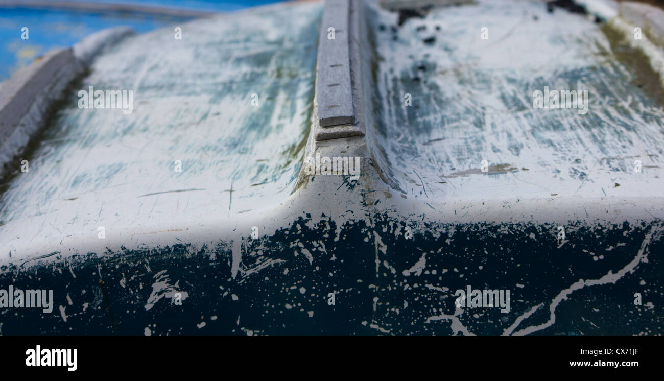 Faded and slightly damaged hull of an upturned rowing boat Stock Photo