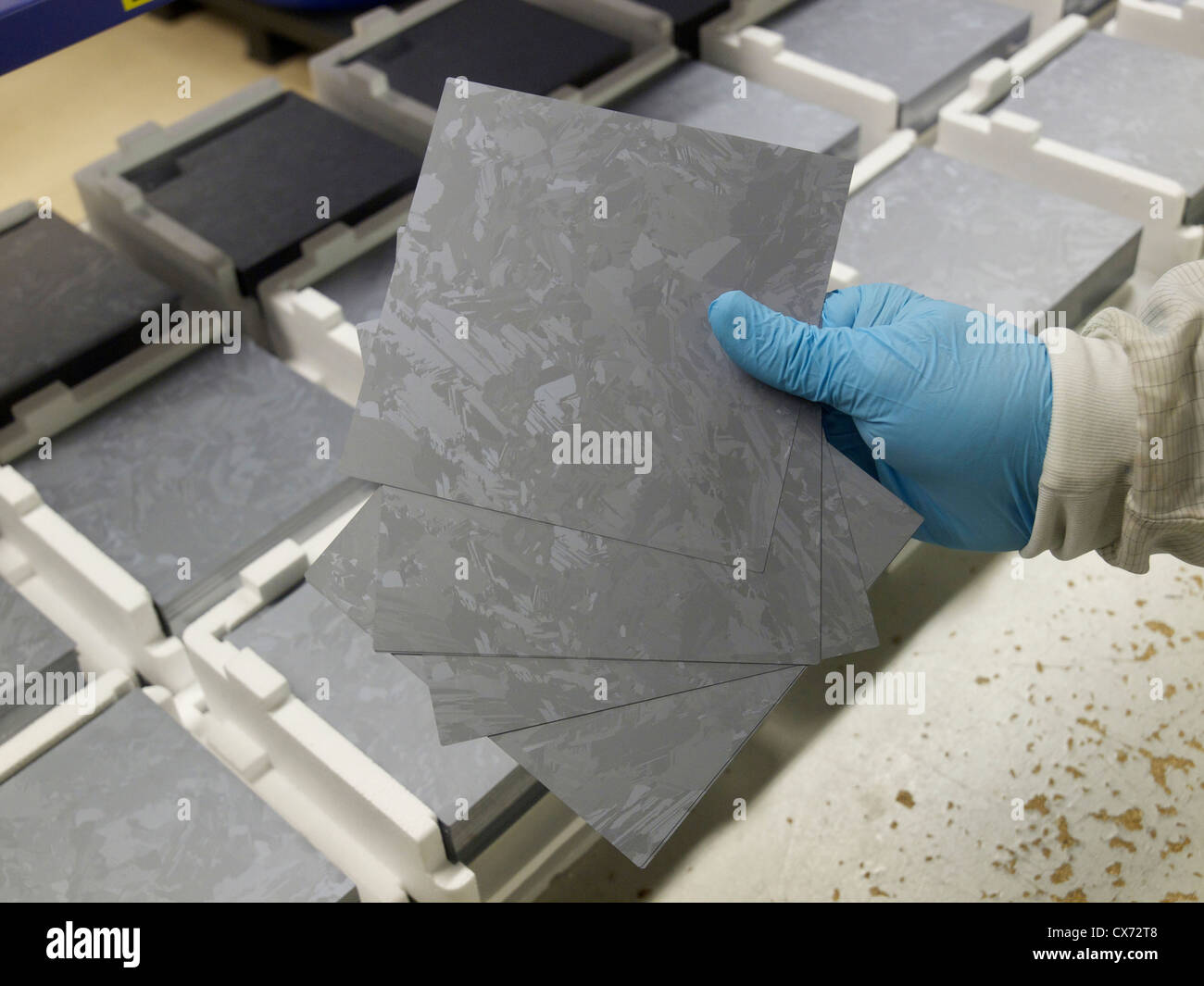 Hand holding 200 micron thick polycrystalline silicon wafers that will be used for solar cell production. - Stock Image