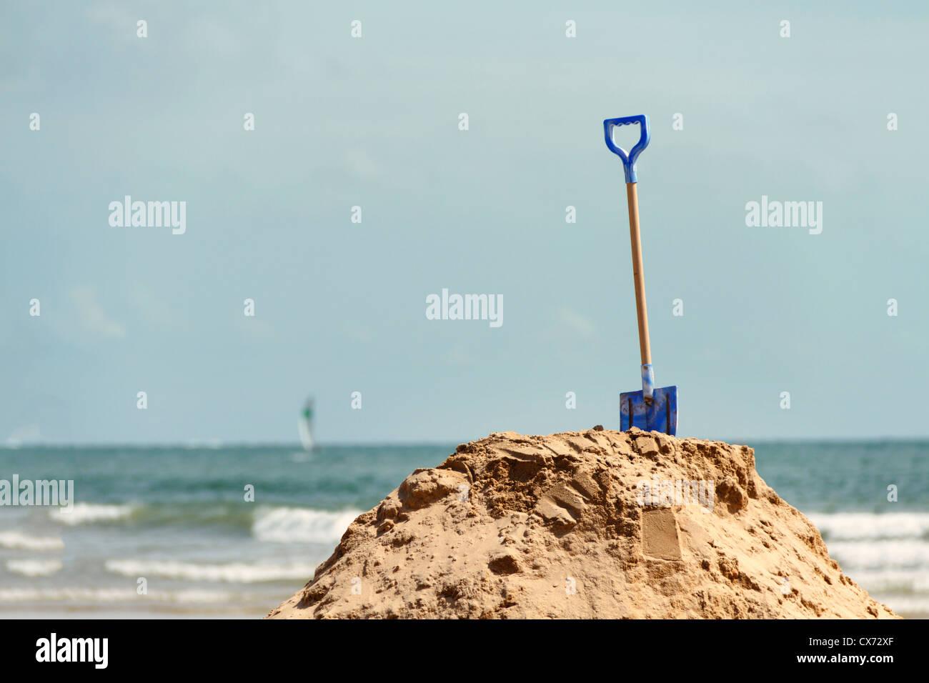 Child's spade in mound of sand, Les Sables-d'Olonne, Vendee, Pays de la Loire, France, Europe. - Stock Image