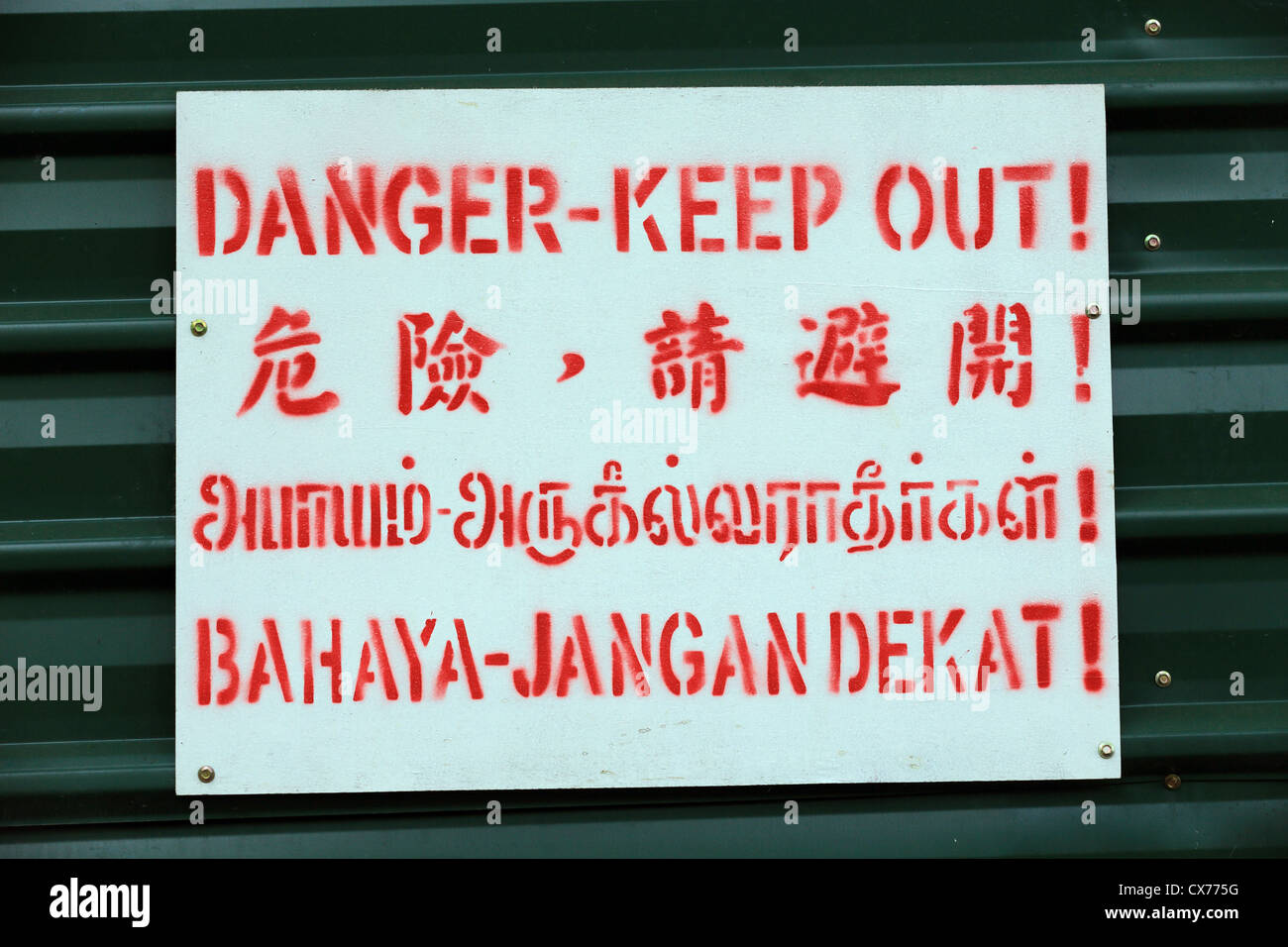 Danger keep out sign in four languages including English and Malay. - Stock Image