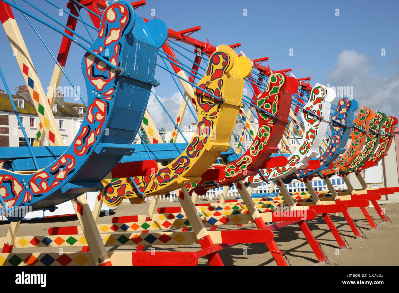 Brightly painted seaside swings on the sea front at Weymouth Dorset - Stock Image