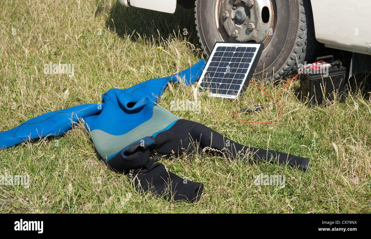 Wet suit and solar panel beside travelers truck. House truckers equipment. Stock Photo