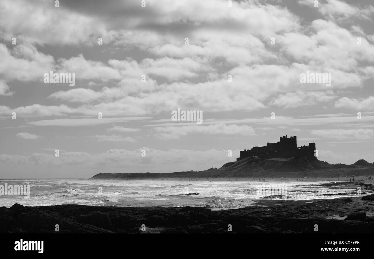 Bamburgh Castle, Northumberland, with waves and people enjoying a Summers day on the beach. Stock Photo