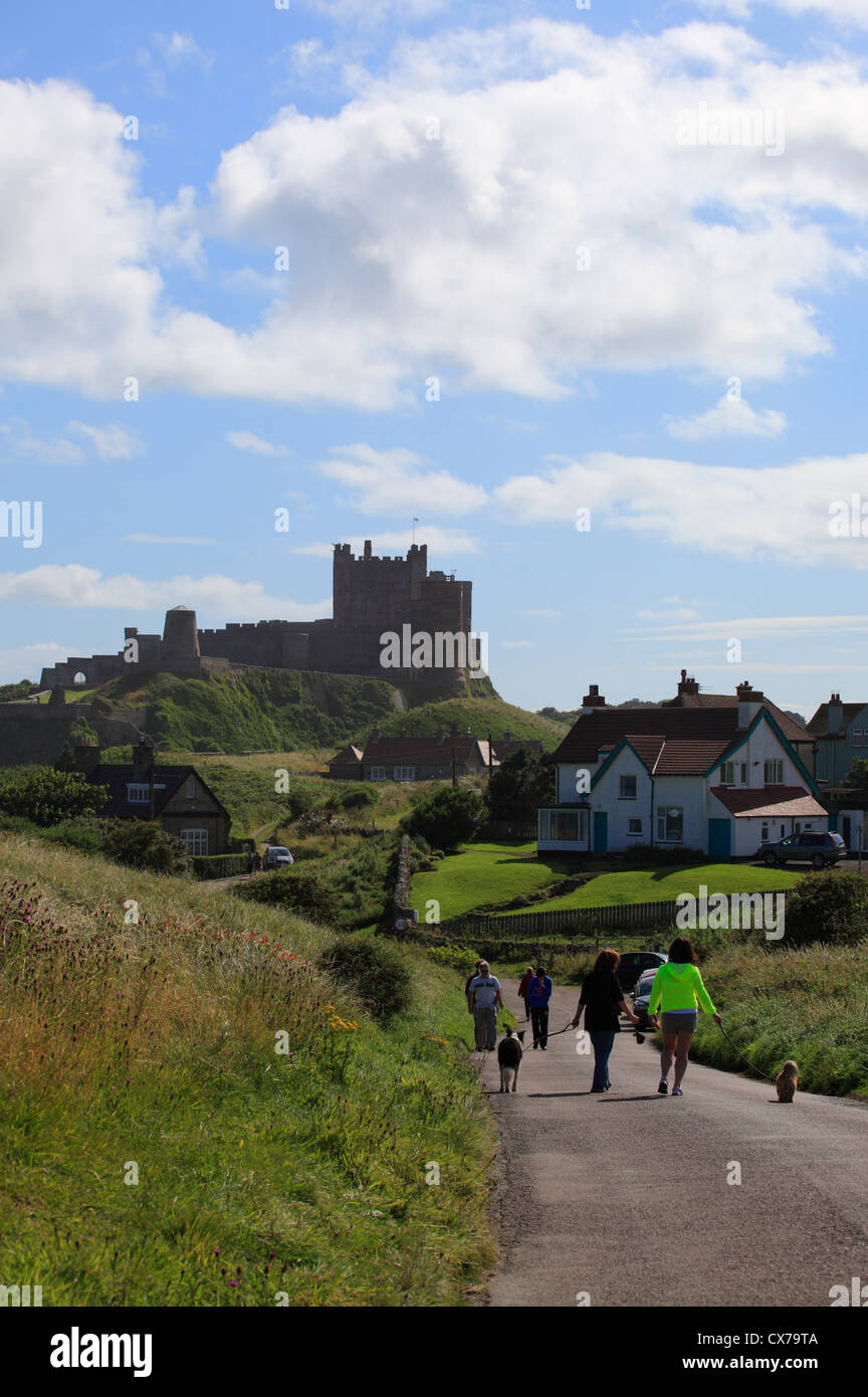 Walkers on the road heading toward Bamburgh Castle on a summers morning in Northumberland. - Stock Image