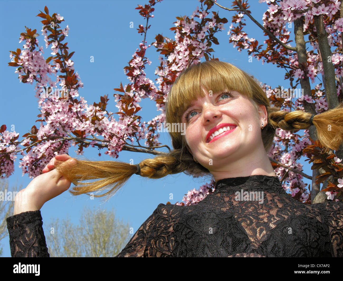young cheerful freckled redheaded woman near the blossoming tree - Stock Image