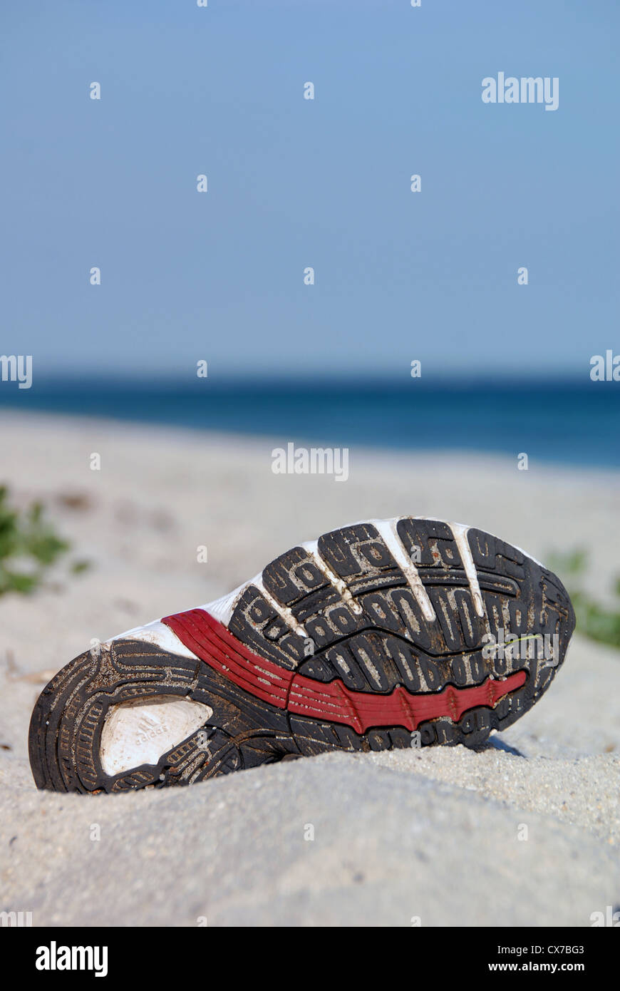 Shoe left on a beach - Stock Image