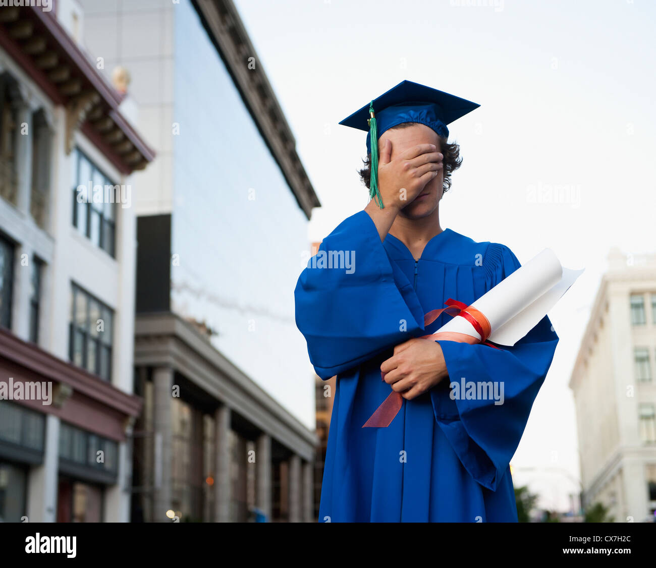A Graduate In Cap And Gown Holds His Hand Over His Eyes; Victoria, British Columbia, Canada Stock Photo