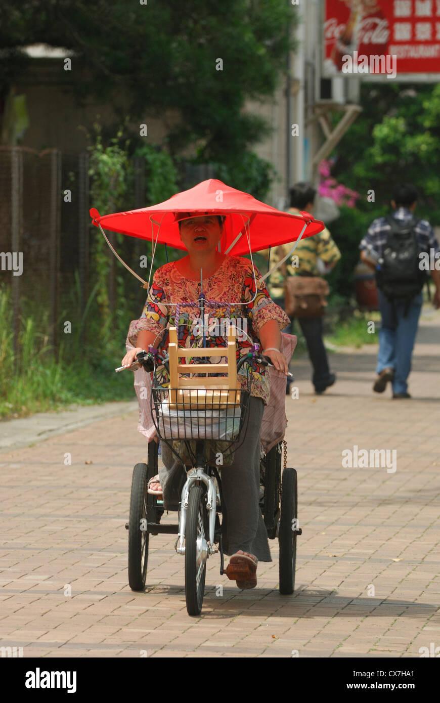 Asian woman with a large umbrella hat riding a trishaw on the street of Mui  Wo Lantau Island China. 205278b5795
