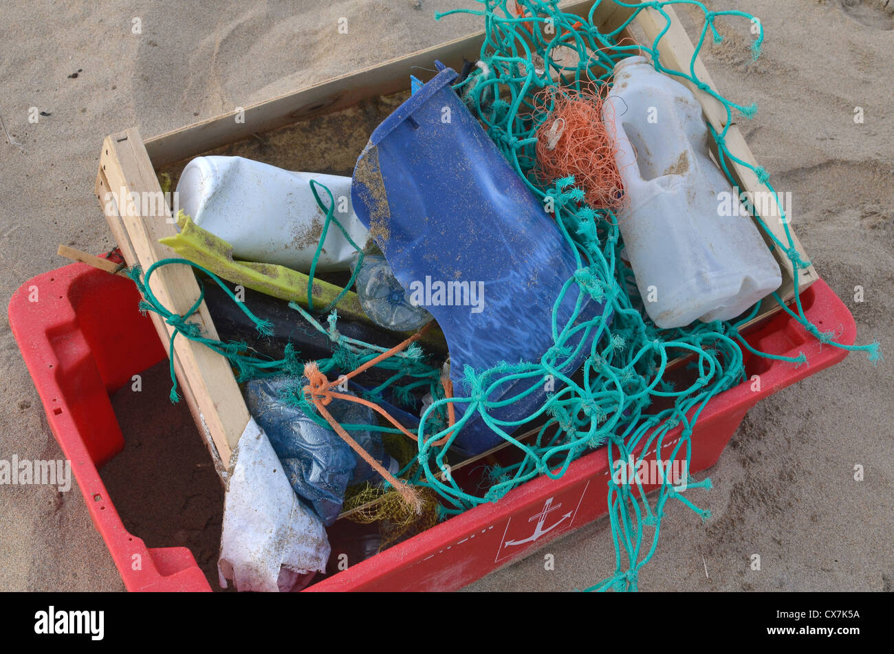 Collection of assorted flotsam / shoreline rubbish on sandy beach. Plastic waste, war on plastic concept. Plastic - Stock Image