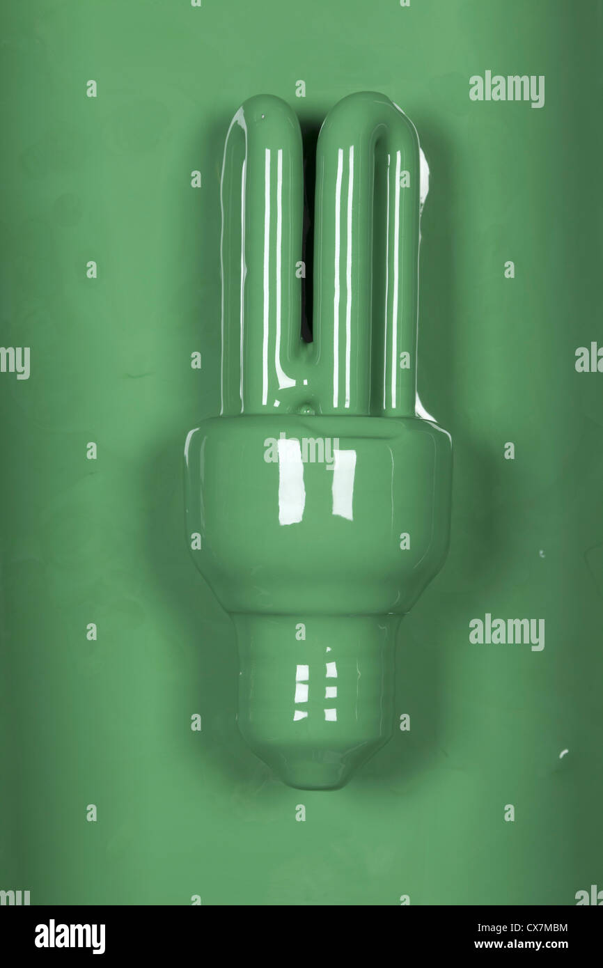 An energy efficient light bulb painted green - Stock Image