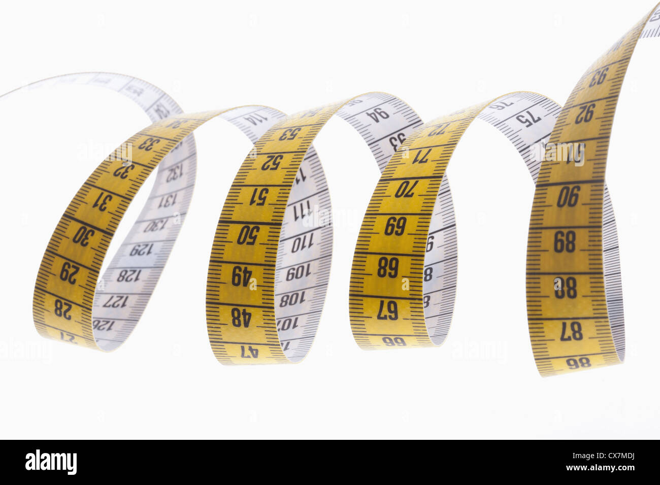 A centimeter tape measure arranged in a spiral shape - Stock Image