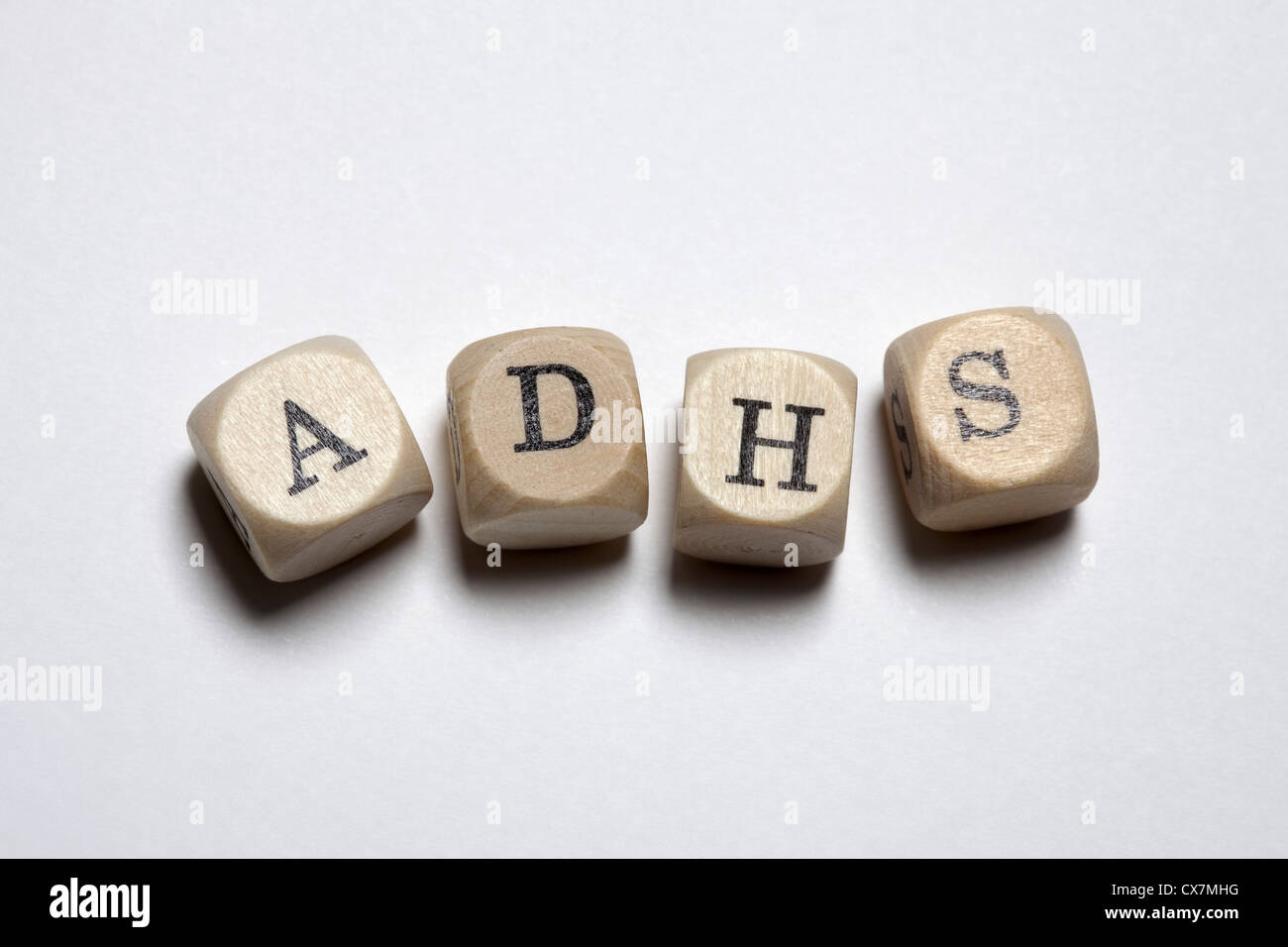 Lettered cubes spelling ADHS, the German acronym for Attention Deficit Hyperactivity Disorder - Stock Image