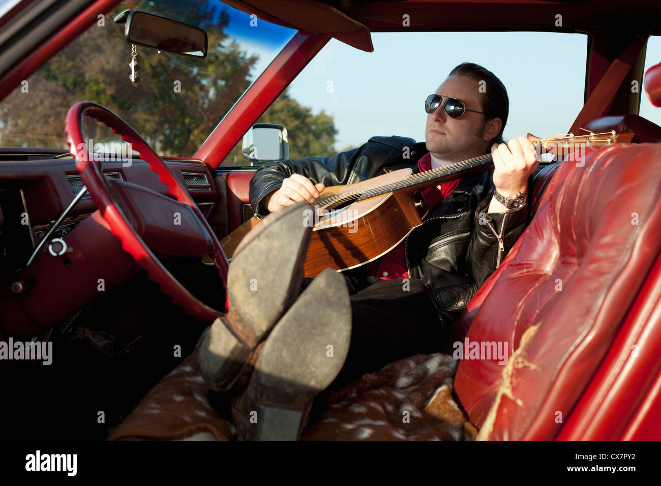 A rockabilly guy playing an acoustic guitar while sitting in his vintage car - Stock Photo