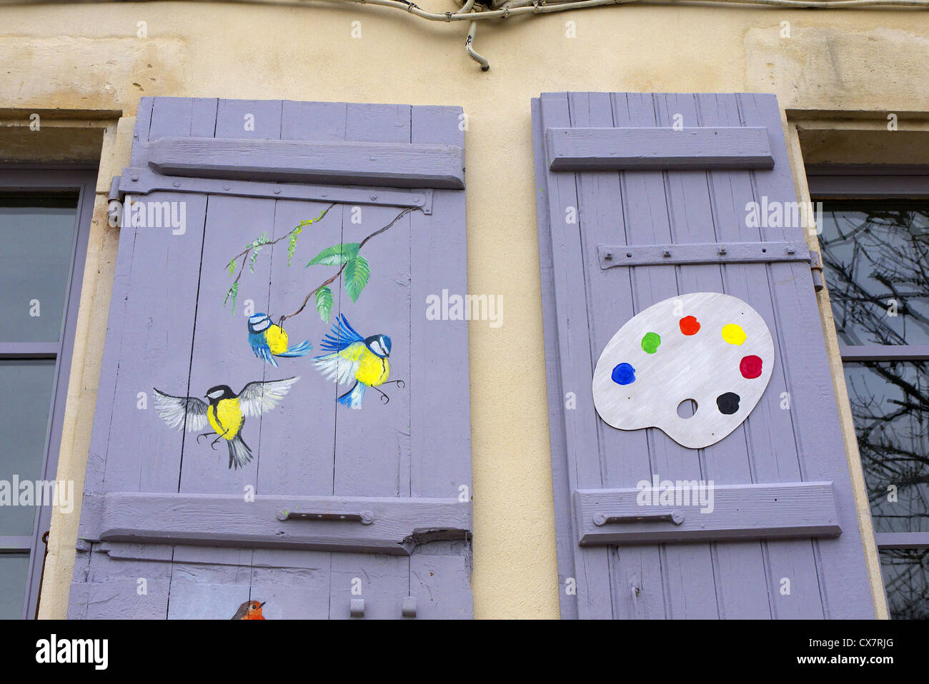Songbirds painted on the shutters of an artist's studio in Fort Brouage, France. - Stock Image