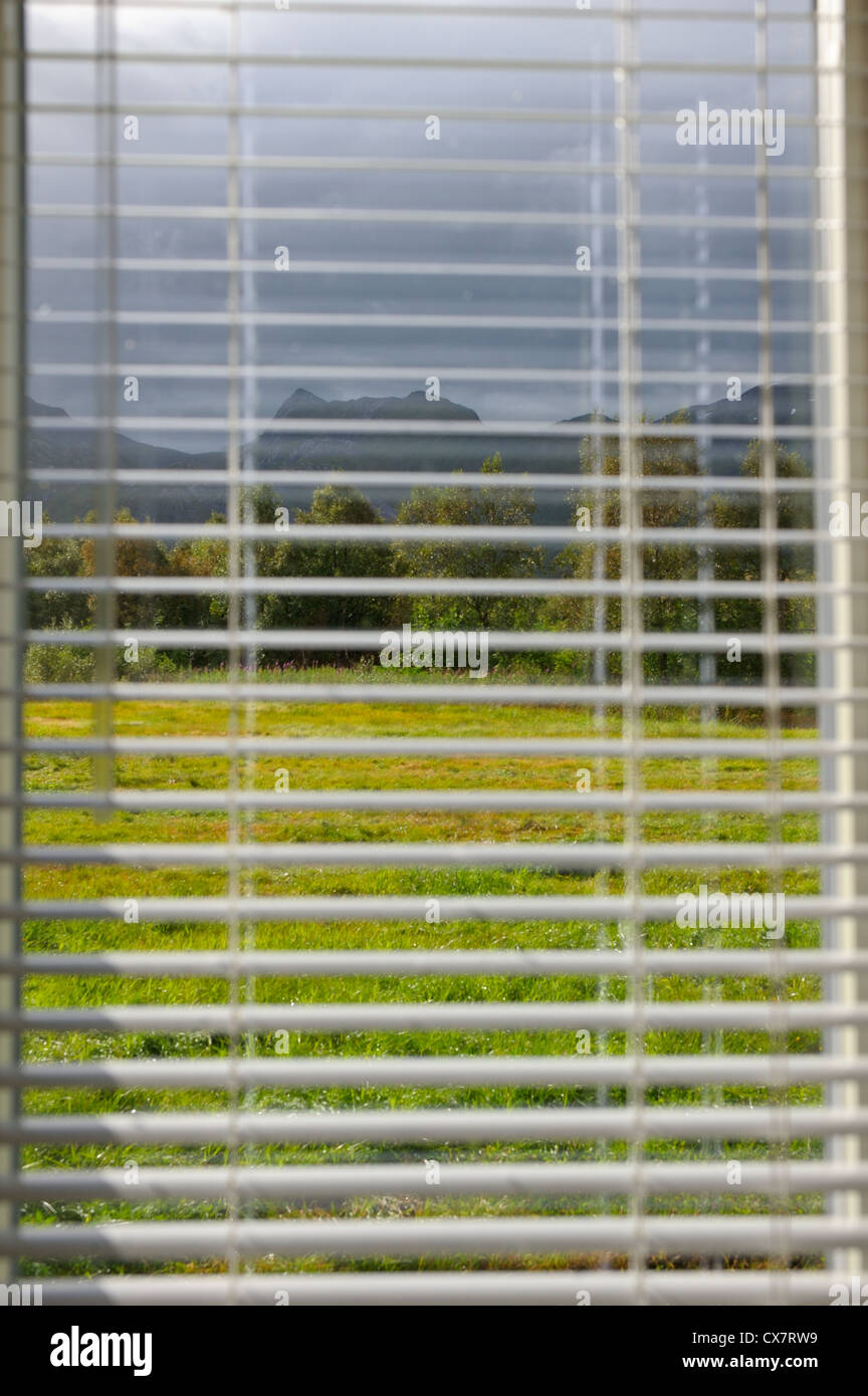 Sunlight after a storm breaks through the blinds - Stock Image