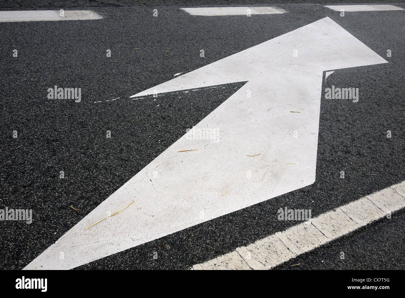 White arrow painted on a road. - Stock Image