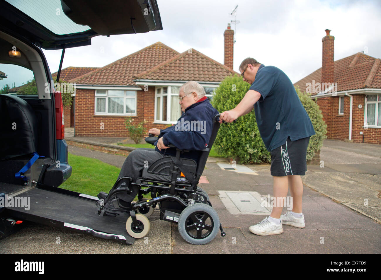Male Carer son pushing a disabled elderly man in a wheelchair onto a built in ramp in a specially adapted car for Stock Photo