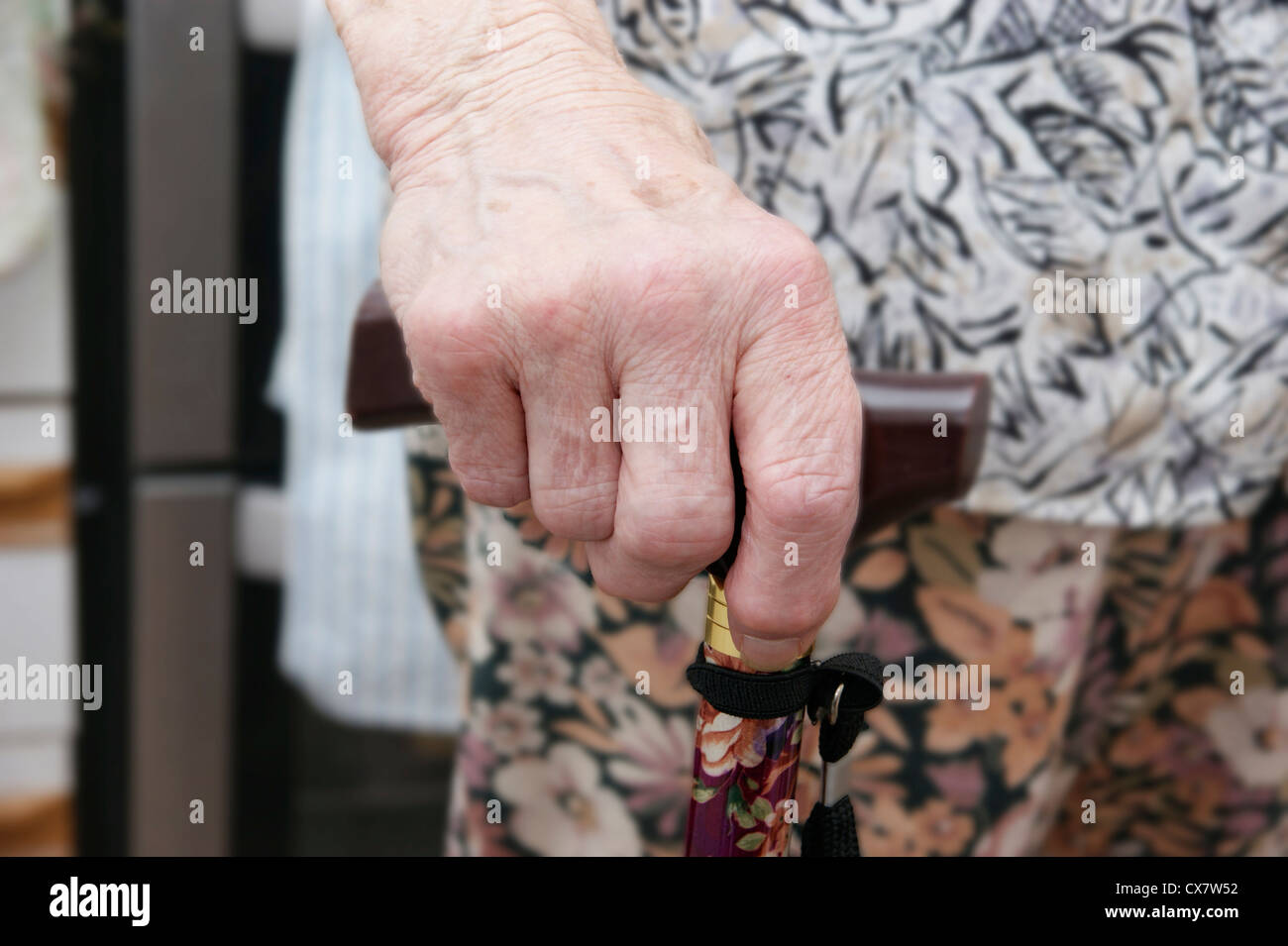 Elderly woman's hand holding a walking stick - Stock Image
