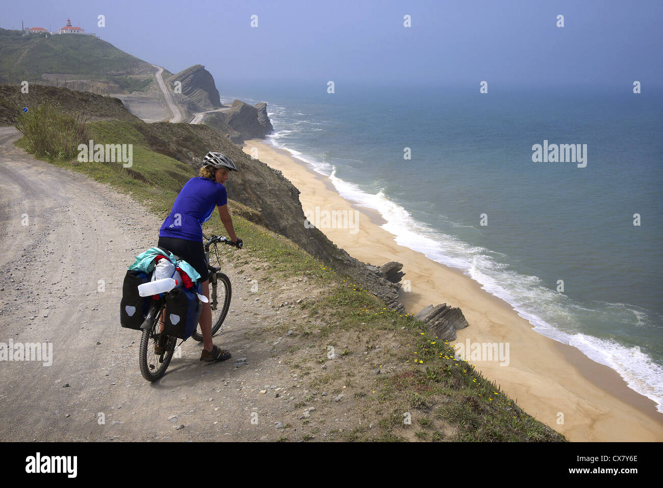A cycle tourist takes in the view near Quiaios in Portugal. - Stock Image
