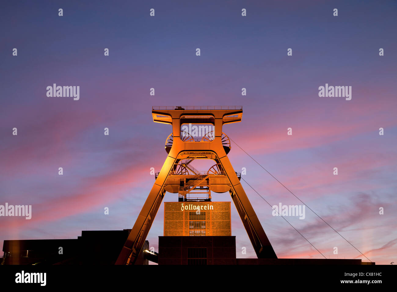 colourful sunset at the winding tower of shaft 12 at Zollverein Coal Mine Industrial Complex in Essen, Germany - Stock Image