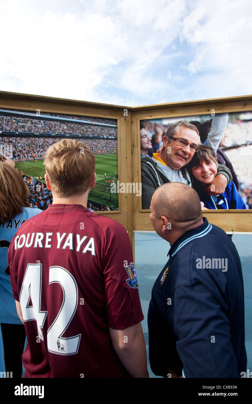 Fans look at the photo-boards outside the Etihad Stadium, Manchester City Football Club, Manchester, England, United - Stock Image