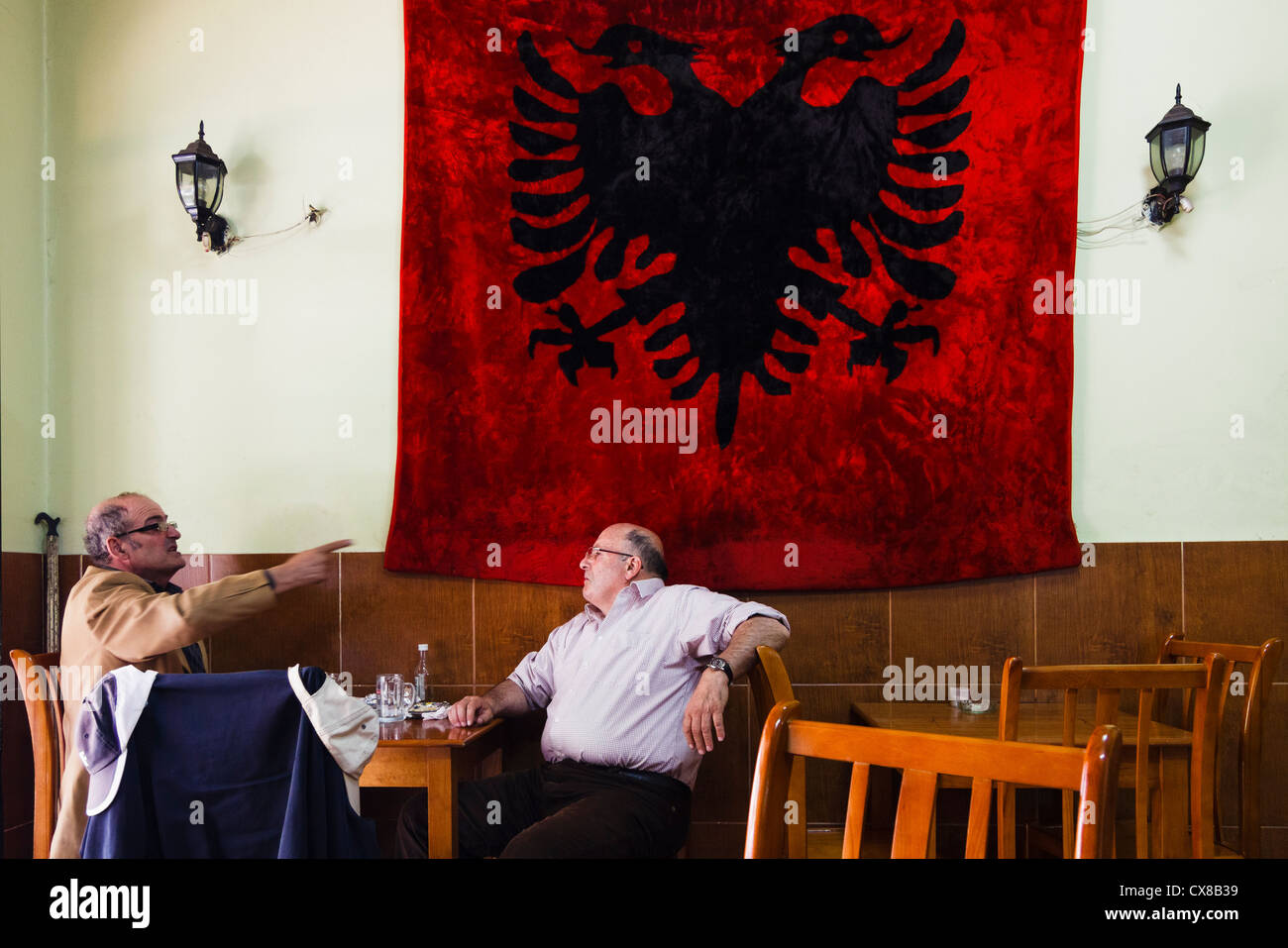 Men talking in a coffeehouse by huge Albanian flag. Tirana, Albania. - Stock Image