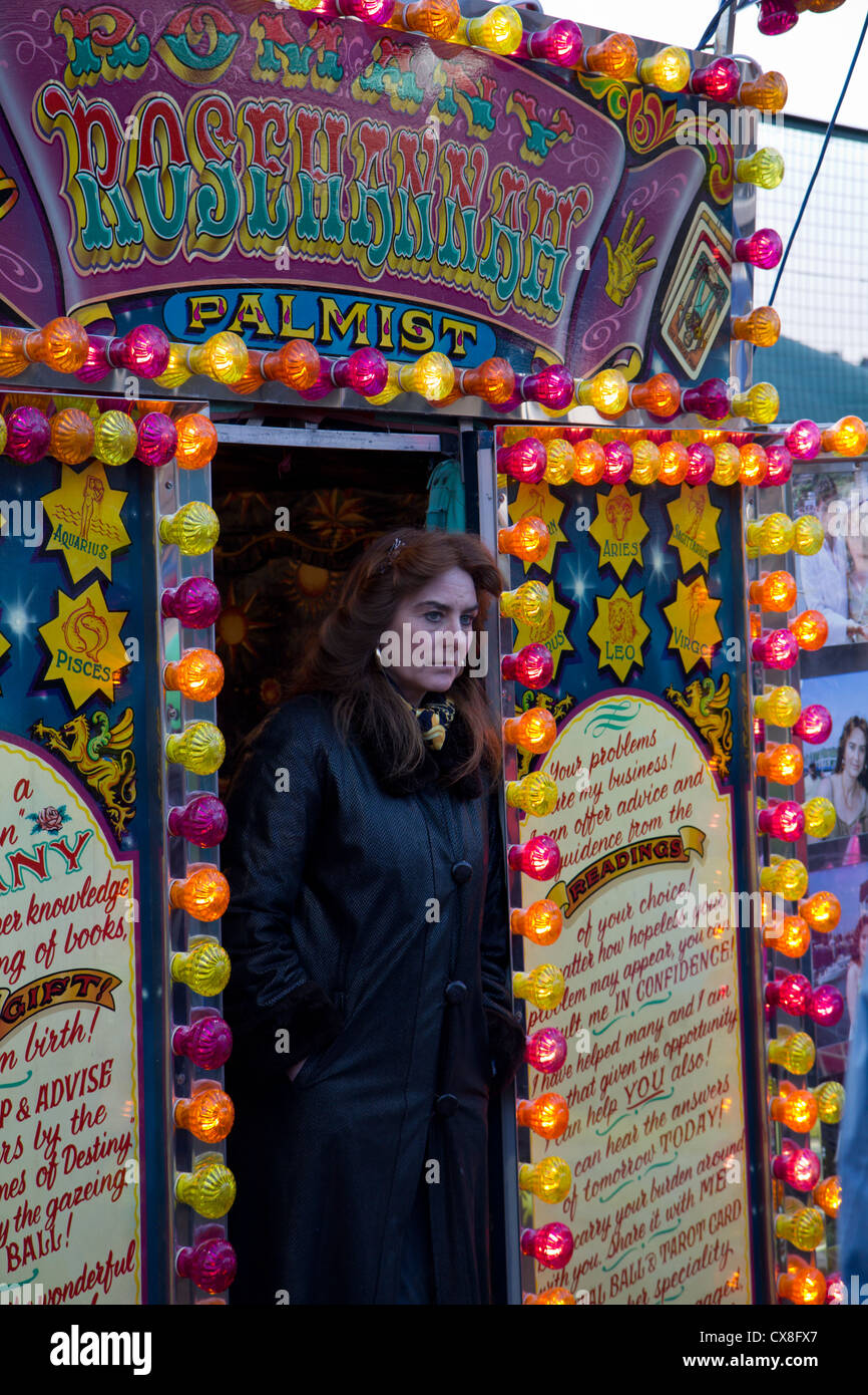 Gypsy fortune teller standing  in doorway waiting for customers at Christmas fair Derbyshire England - Stock Image