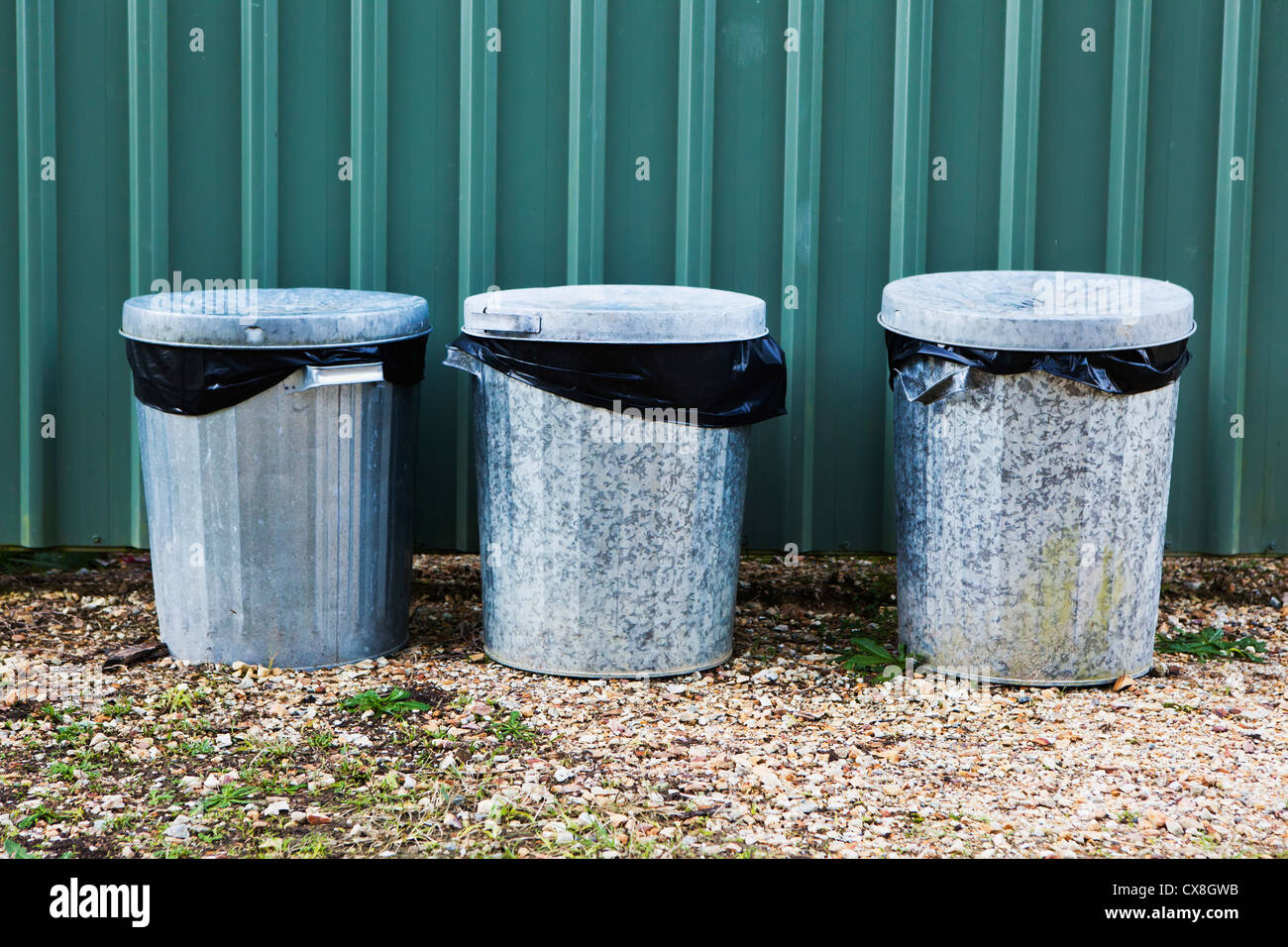 Metal Garbage Bins In A Row Against A Metal Wall; Murwillumba New South Wales Australia - Stock Image