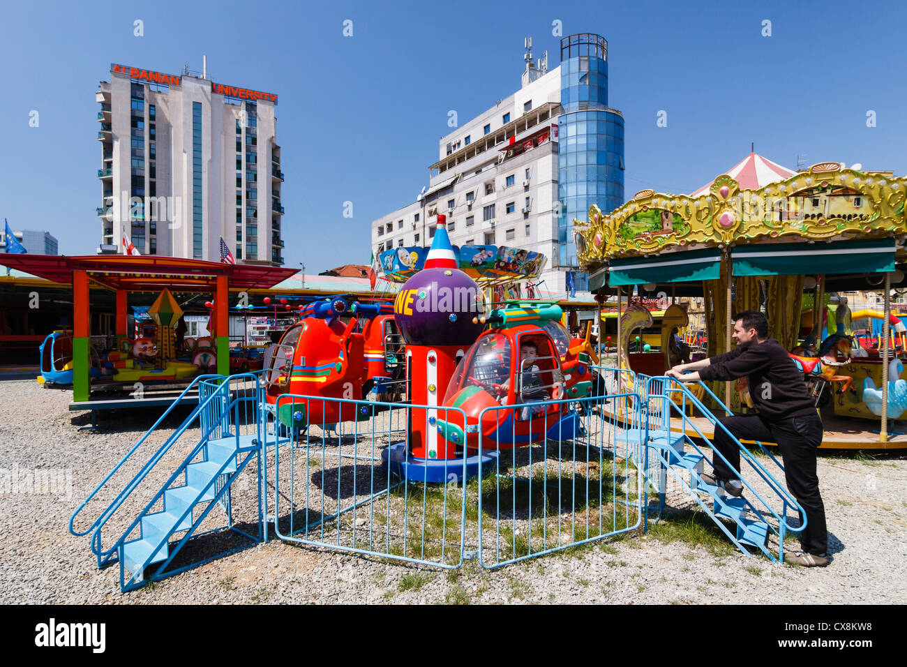 Carousel and small funfair by Albanian University building in downtown Tirana, Albania - Stock Image